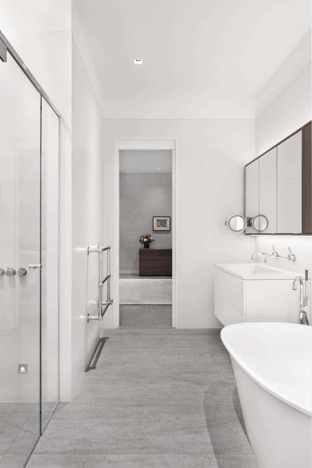 Open plan bathroom offers a walk-in shower and freestanding tub next to the floating sink vanity with chrome faucets and medicine cabinet.