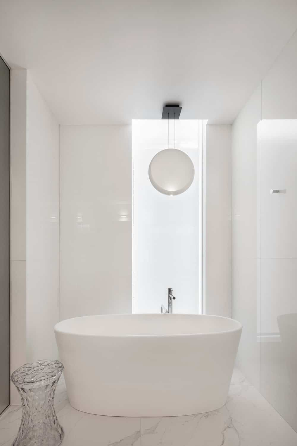 An all-white bathroom with a freestanding bathtub accompanied by a round pendant and a fancy glass stool that sits on marble tiled flooring.