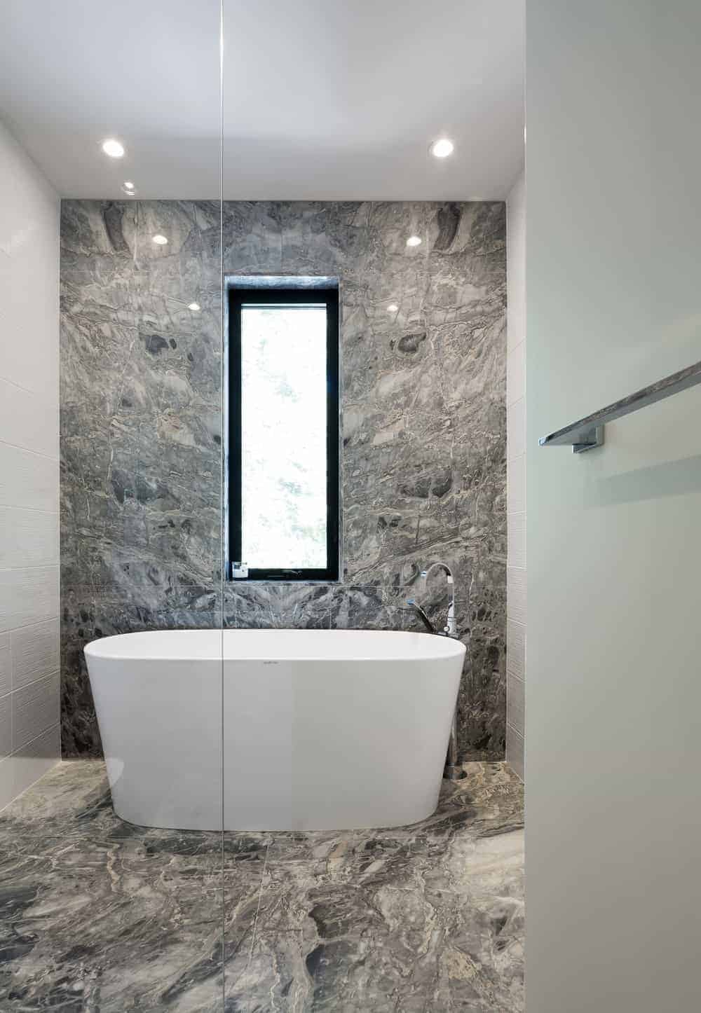 Deluxe bathroom features a deep soaking tub on a gray marble flooring that matches with the accent wall fitted with an aluminum framed glass window.