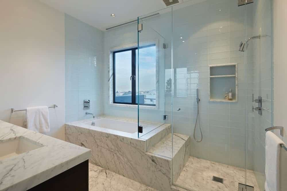 White master bathroom with walk-in shower enclosed in frameless glass and a drop-in tub clad in marble that match the flooring and countertop.