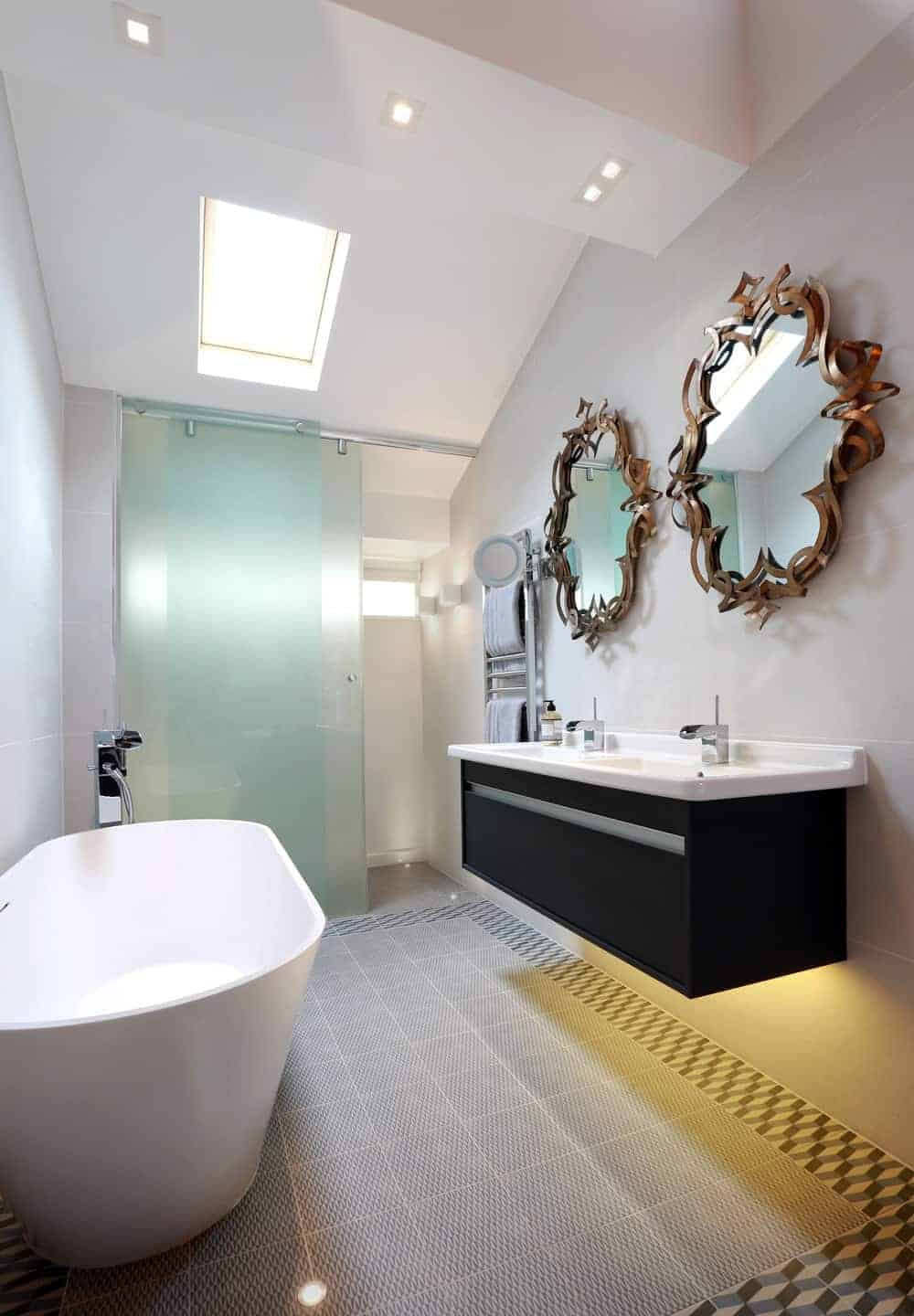 A freestanding tub sits across the black floating vanity with dual sink and stylish mirrors in this magnificent bathroom with a skylight and pattern tiled flooring bordered with geometric tiles.