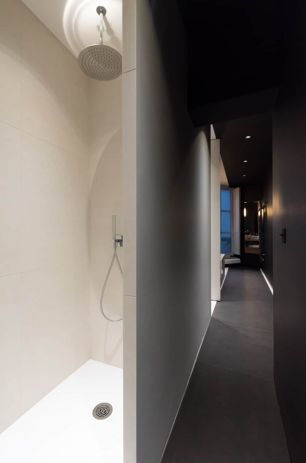 A small bathroom along the dark hallway clad in white ceramic tiles offering chrome shower head and sprayer.