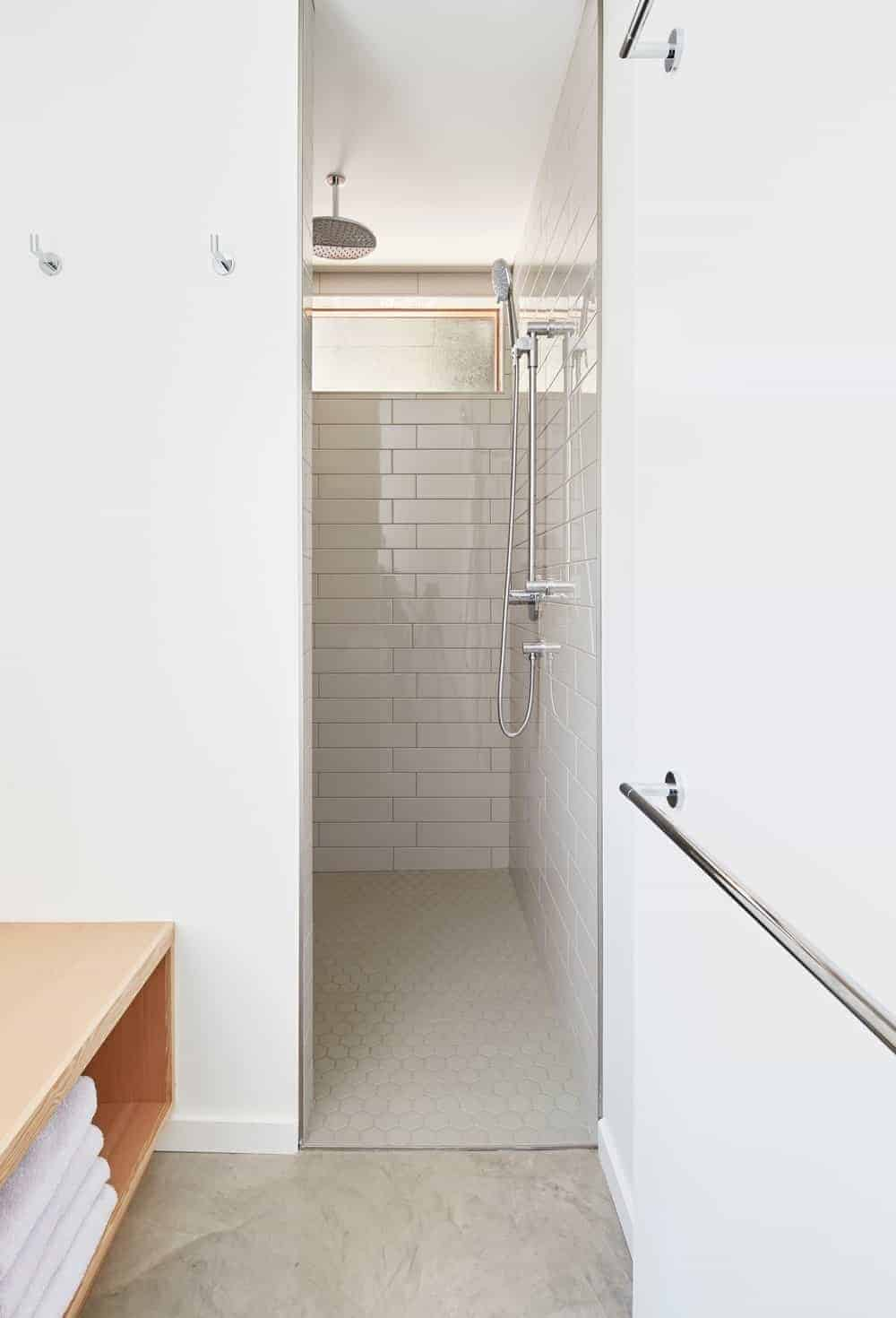White bathroom showcases a wooden shelf and a walk-in shower with white subway tile walls and hex flooring.