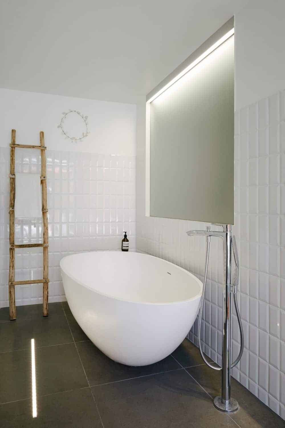 Gorgeous white bathroom with half tiled walls and freestanding tub on black flooring accompanied by a chrome faucet and rustic ladder that serves as a towel rack.