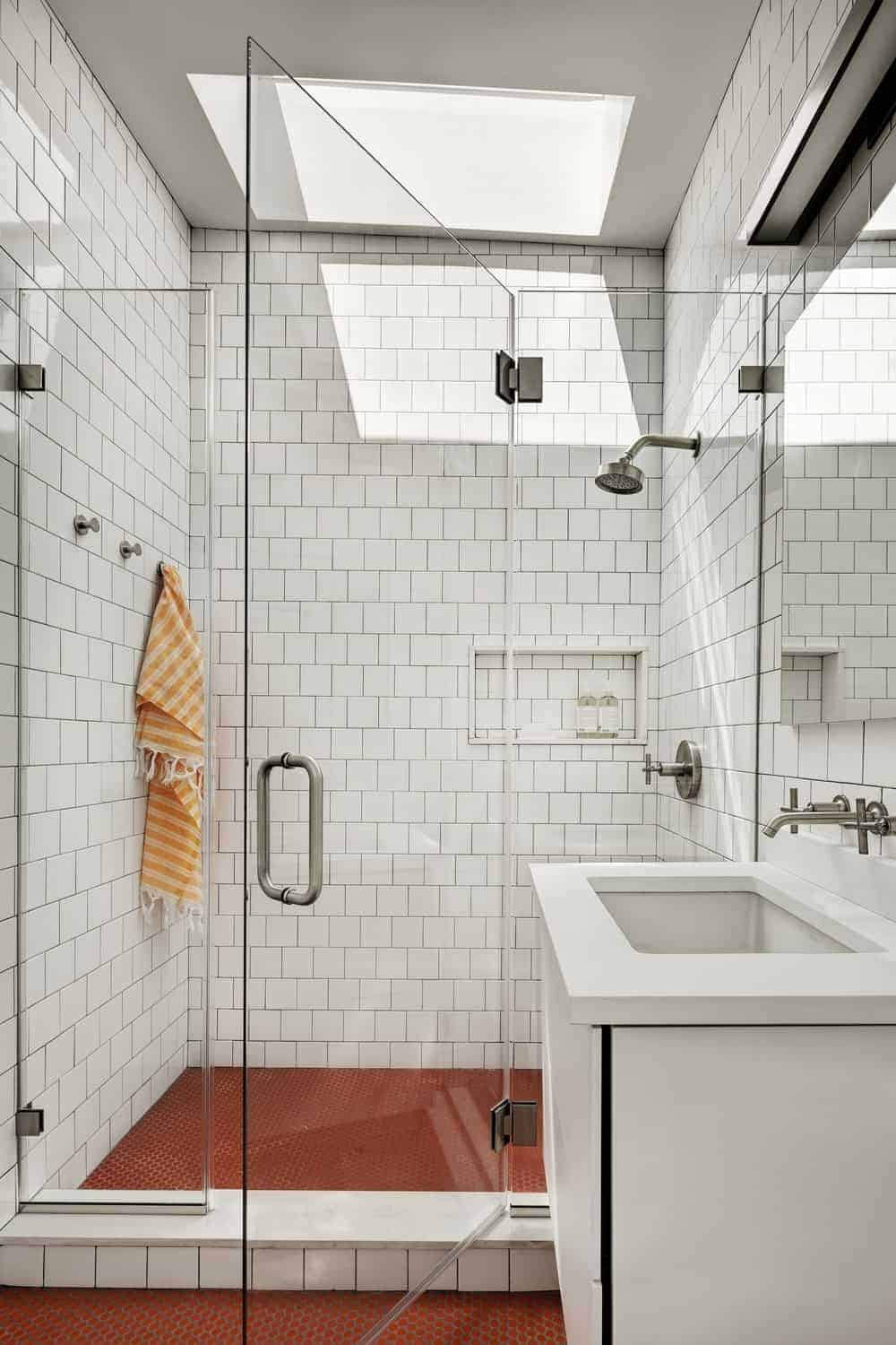 Classic bathroom with sleek sink vanity and walk-in shower surrounded by white tiled walls and glass enclosure. Red hex flooring adds a nice striking contrast to the white bathroom.