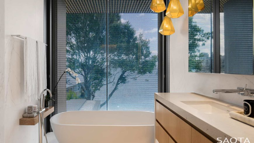 Yellow diamond pendant lights illuminate this master bathroom showcasing a light wood sink vanity with granite countertop and a freestanding tub by the floor to ceiling window.