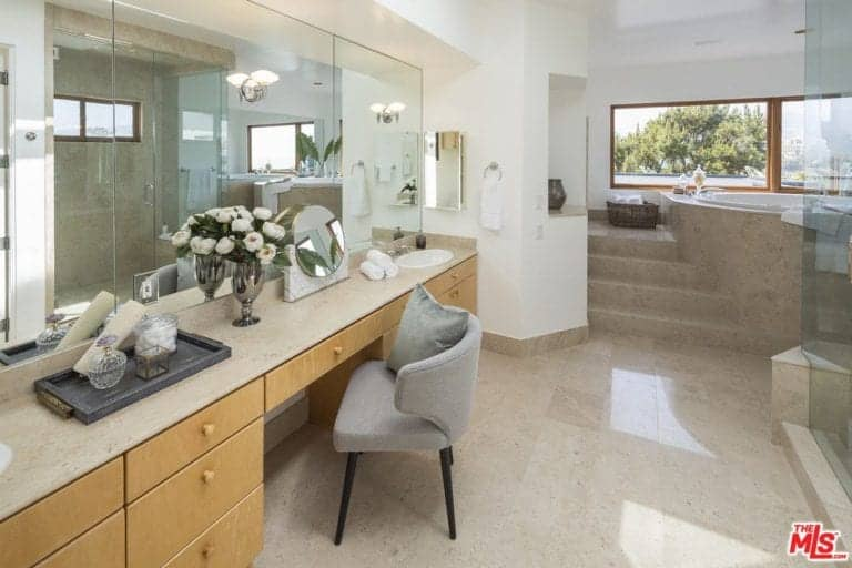A gray wingback chair sits at a light wood vanity with marble countertop and porcelain sink in this master bathroom offering a walk-in shower and drop-in tub.