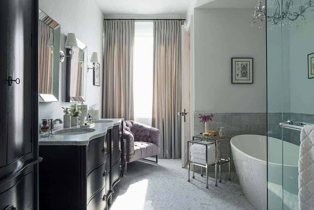 Luxury master bathroom illuminated by a fancy chandelier that hung over the freestanding tub with a modular table on the side. It includes a tufted round back chair and dark wood dual sink vanity paired with mirrors and sconces.