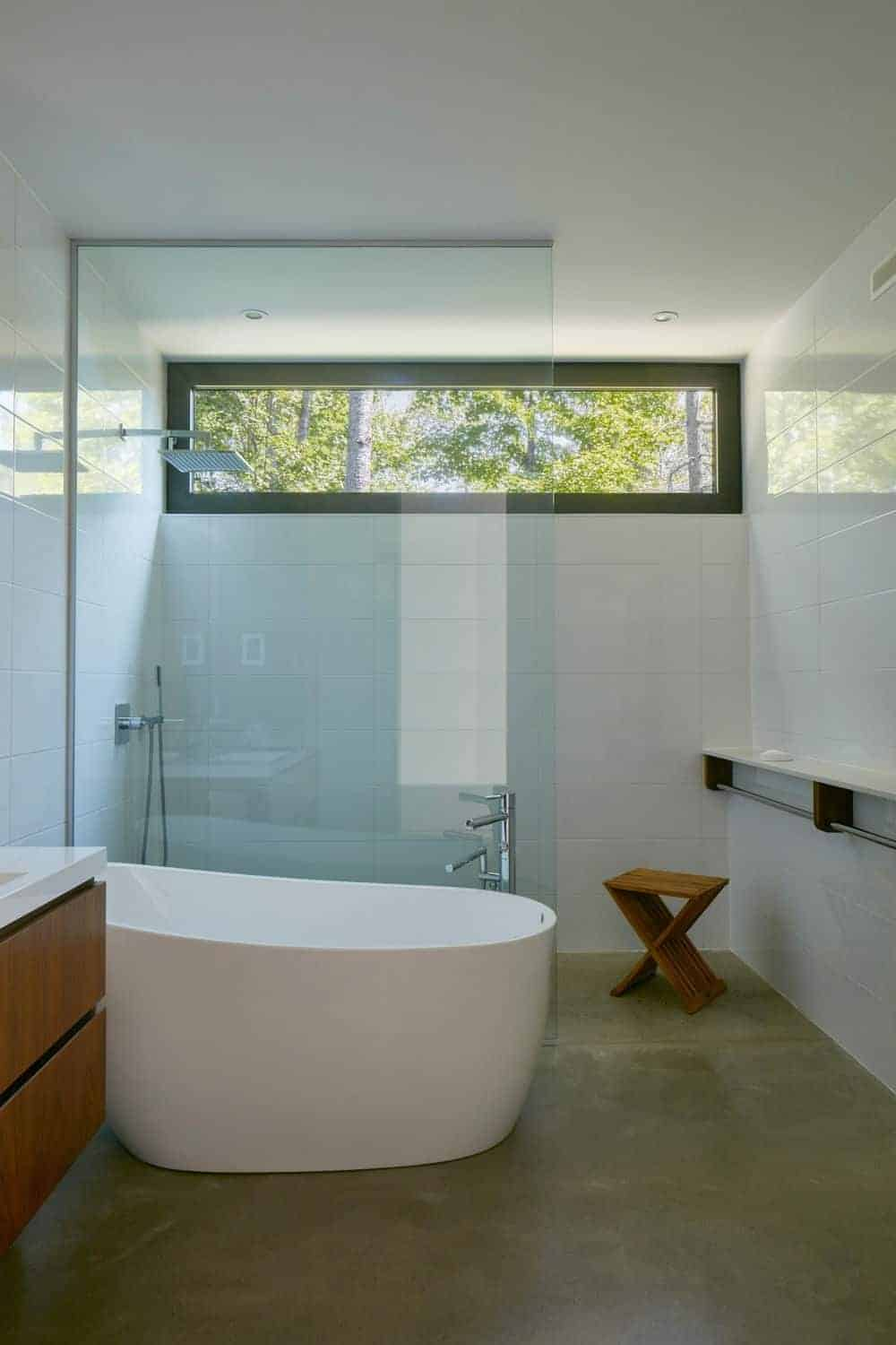 Fresh bathroom with a walk-in shower and deep soaking bathtub that sits on concrete flooring. It includes a marble shelf with rods and a wooden stool that complements with the floating sink vanity.