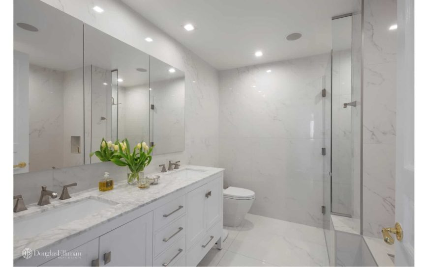 Marbled bathroom with a walk-in shower and toilet that sits next to the dual sink vanity with chrome hardware and mirrored medicine cabinets.