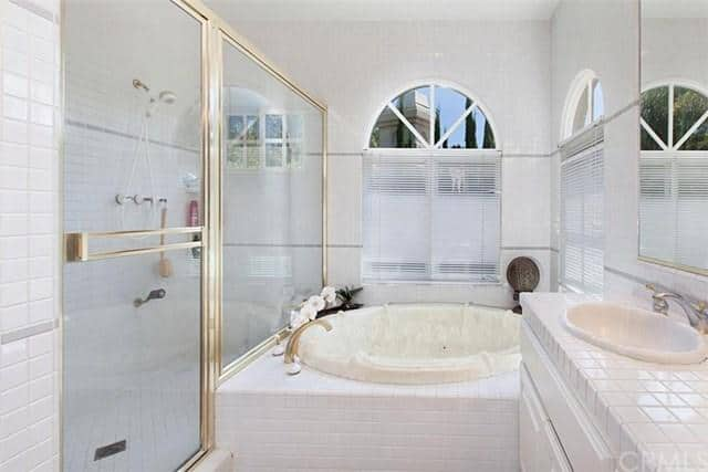 Stylish master bathroom boasts a tiled vanity and walk-in shower accented with gold linings. It includes a deep soaking tub situated beneath the arched windows covered in white blinds.