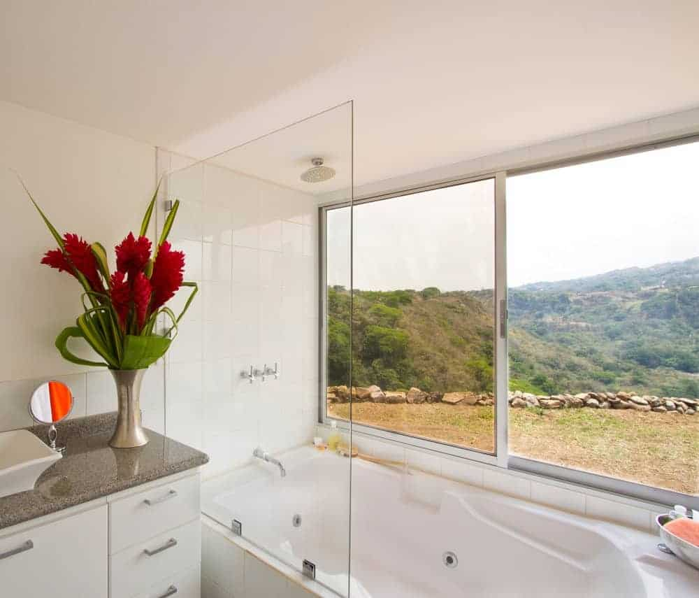 A vessel sink vanity topped with granite counter and lovely flower vase sits next to the shower and tub combo in this white bathroom with a panoramic window overlooking the outdoor scenery.