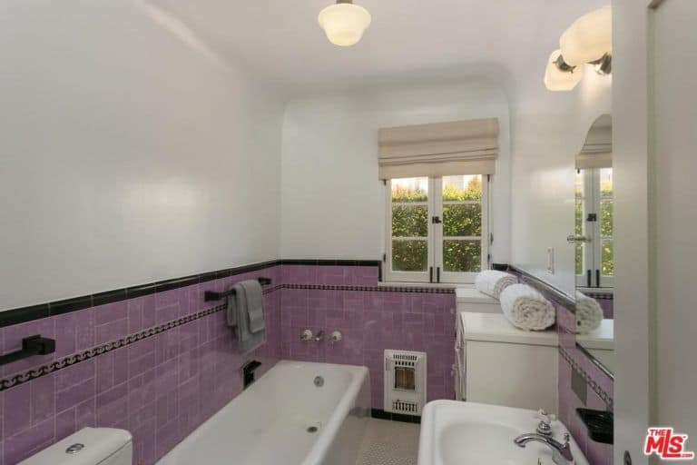 Charming master bathroom with hex tiled flooring and white framed window covered in beige roman shade. It has a porcelain sink and deep soaking tub placed against the purple tiled lower wall.