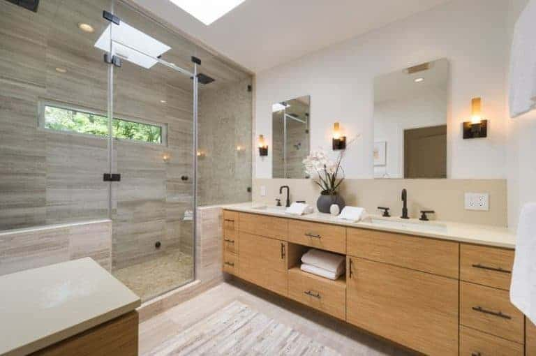 A wooden sink vanity sits beside the walk-in shower in this master bathroom with a skylight reflected in the glass enclosure and frameless mirrors flanked by warm sconces.