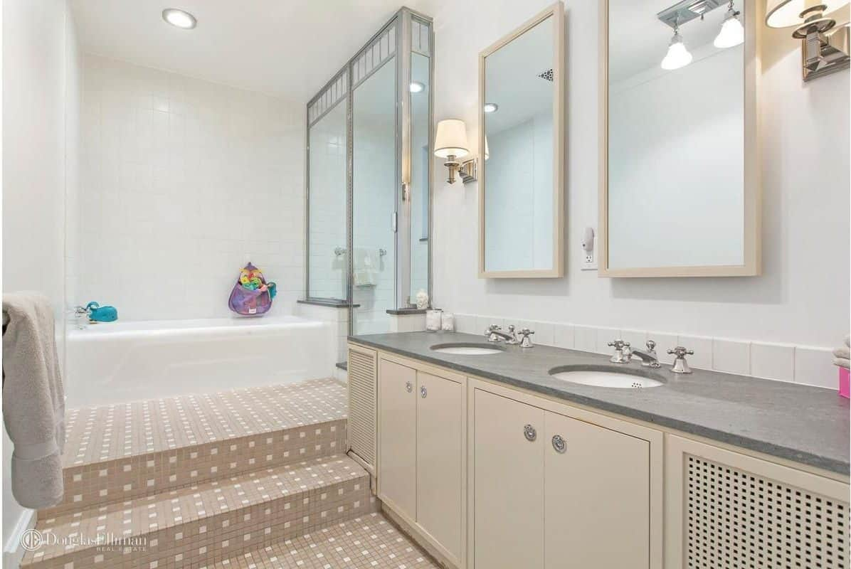 Classic white master bathroom boasts a beige dual sink vanity along with a striking tiled flooring and stairs leading to the drop in bathtub and walk-in shower.