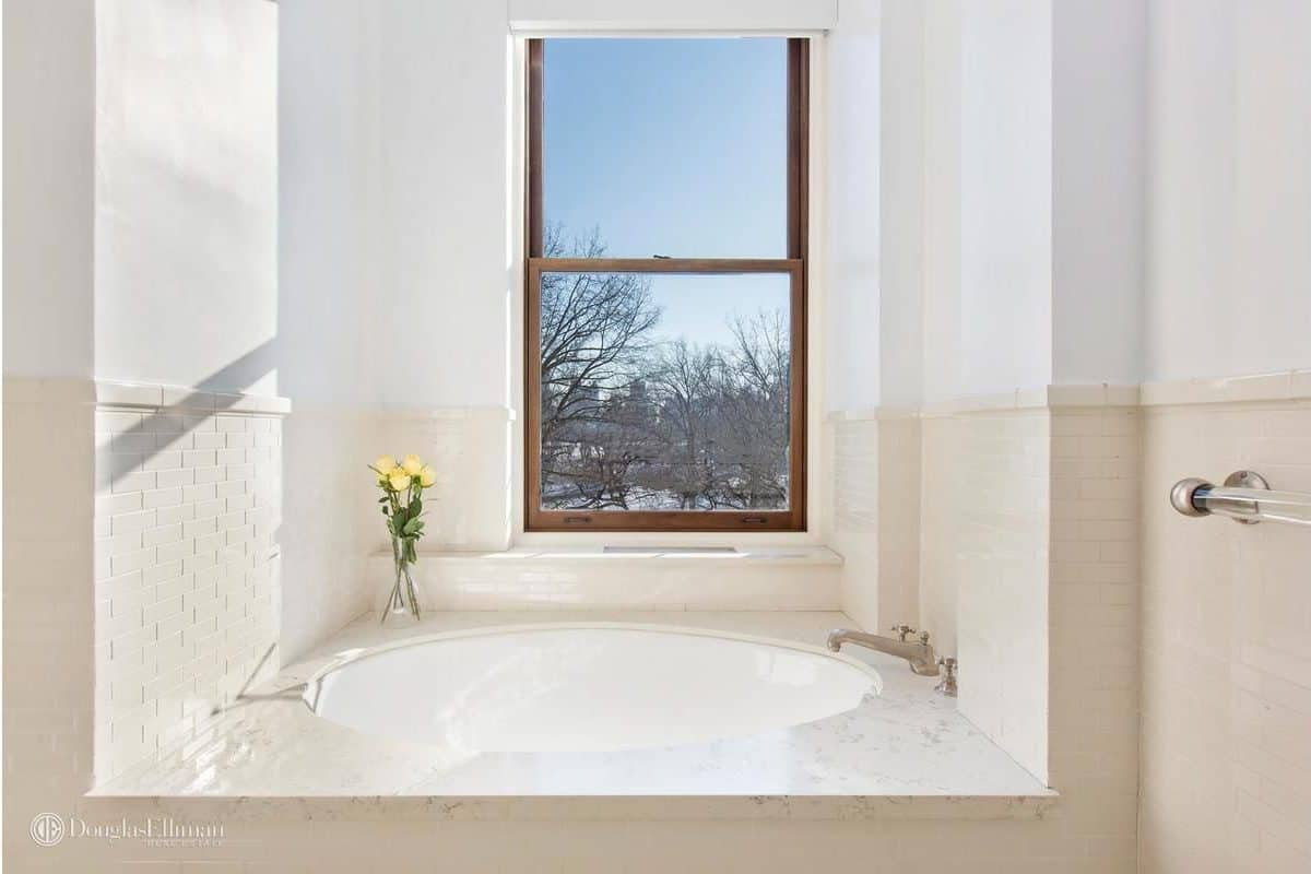 Bright bathroom features a deep soaking tub clad in white marble and bricks. It is situated underneath a wooden framed window overlooking the outdoor scenery.