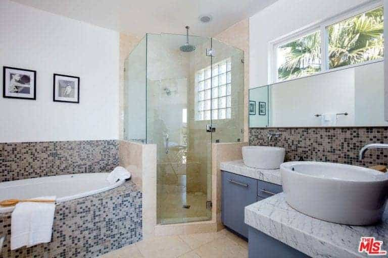Gorgeous master bathroom offering a walk-in shower in between grayish blue vanities and deep soaking tub clad in stunning mosaic tiles.