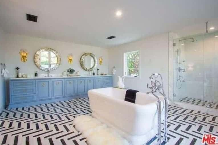 Fabulous master bathroom showcases a blue vanity paired with gorgeous round mirrors and sconces. It includes a pedestal tub with a white faux fur runner on the side that sits on striking tiled flooring.