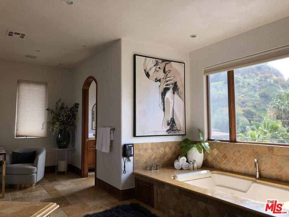 Spanish style bathroom decorated with an interesting wall art mounted above the drop in bathtub. It has a gray round back chair and fresh potted plants that bring a tropical vibe in the room.