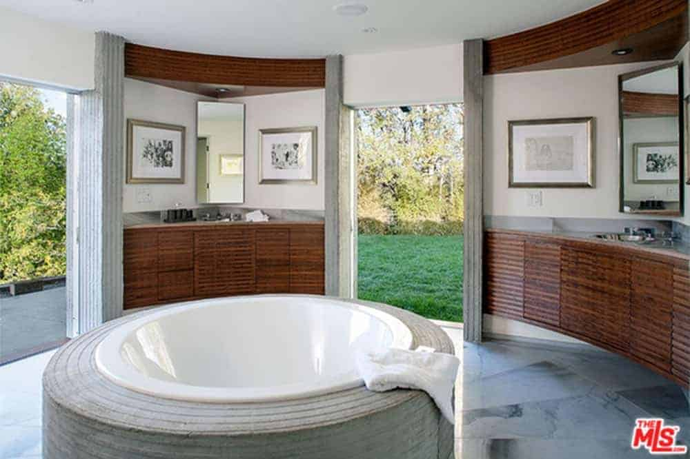 This master bathroom features a concrete tub surrounded with wood plank vanities and open doorways leading out to the lush green yard filled with abundant plants.