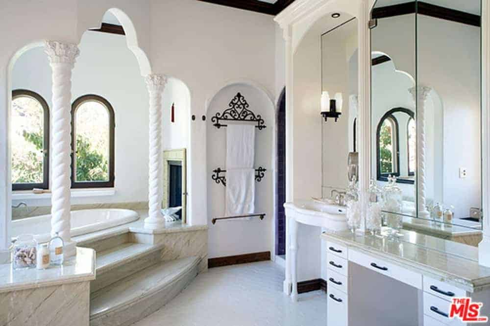 Mediterranean master bathroom showcases a porcelain washstand next to the vanity and an alcove tub lined with spiral columns. It includes a black ornate towel rack fitted on the arched inset wall.