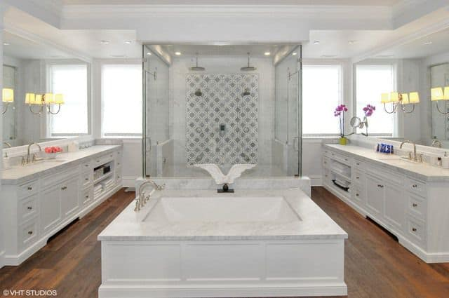 Deluxe master bathroom with a walk-in shower and deep soaking tub in between single sink vanities. It has natural wood plank flooring and mirrored walls mounted with traditional sconces.