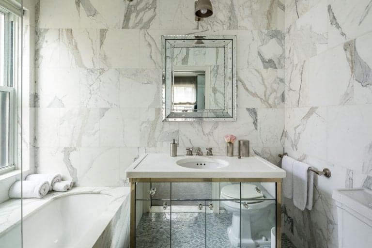 The marbled bathroom offers a drop in bathtub and mirorred sink vanity topped with a quartz counter and paired with a glam mirror lighted by a vintage wall sconce.