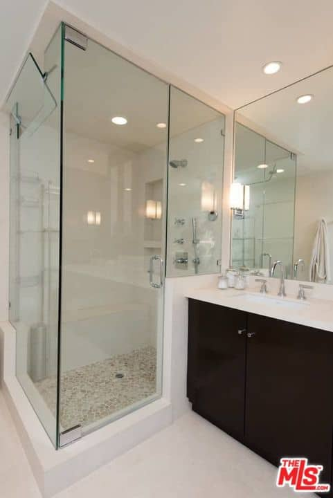 White master bathroom contrasted with a dark wood sink vanity that sits beside the walk-in shower enclosed in glass.