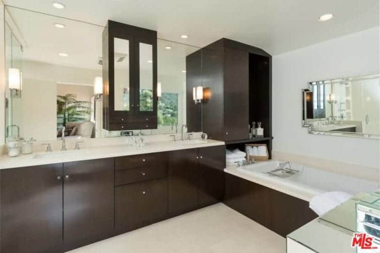This master bathroom boasts dark wood cabinetry that matches with the drop in bathtub paired with a beveled mirror.