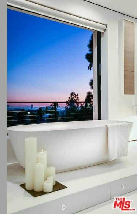 Light and airy master bathroom features a freestanding bathtub with various sized candles on the side for a relaxing and soothing bath you never had.