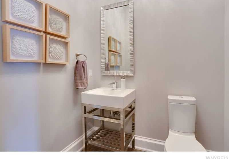Charming master bathroom decorated with wooden framed wall arts and a textured mirror that hung above the stainless steel washstand sitting next to the toilet.