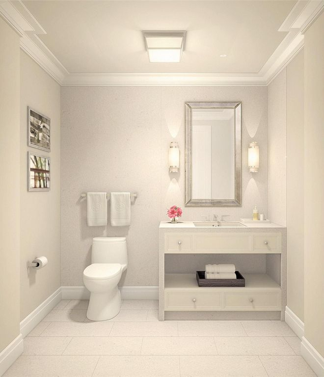 Clean white bathroom illuminated by wall sconces and a flush light mounted on the ceiling lined with crown molding. It has a toilet and sink vanity accented by a beveled mirror.