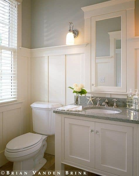 Fresh bathroom with louvered window and light blue wall clad in white wainscoting that blending in with the medicine cabinet and sink vanity topped with a granite counter.