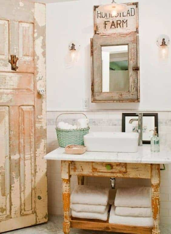 Rustic powder room showcases a distressed door that complements the sink vanity topped with marble counter and vessel sink. It includes a wooden medicine cabinet illuminated by wall sconces and pendant light.
