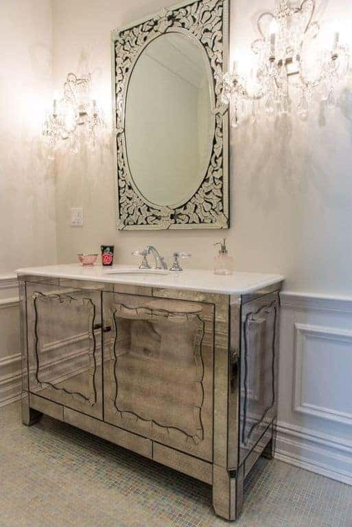 Deluxe powder room with mirrored sink vanity against white wainscoting and a glamorous ornate mirror flanked by crystal sconces.