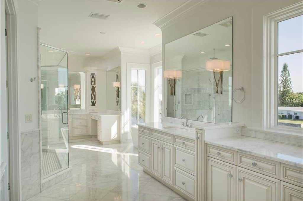 An all-white master bathroom with a glass enclosed shower area and sink vanities topped with marble counters and frameless mirrors that are lighted by wall sconces.