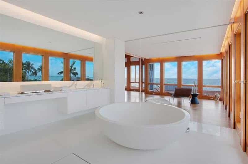 Minimalist bathroom with a sleek vanity and a round tub surrounded by full height glazing that overlooks a breathtaking ocean view.