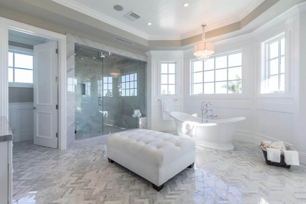 Elegant master bathroom features herringbone tile flooring and tray ceiling mounted with recessed lights and a fabulous chandelier. It has a freestanding tub and a tufted ottoman across the walk-in shower clad in gray marble.