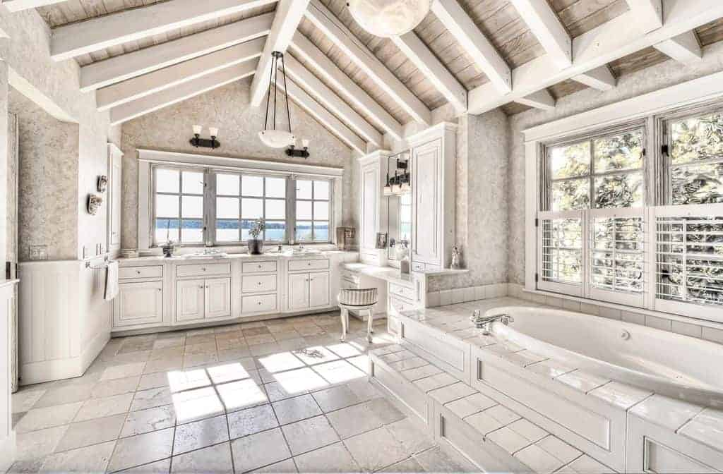Rustic master bathroom with white cabinetry and a drop in bathtub matching with the white tiled flooring. It is illuminated by black sconces and classic pendant lights that hung from the wood beam ceiling.