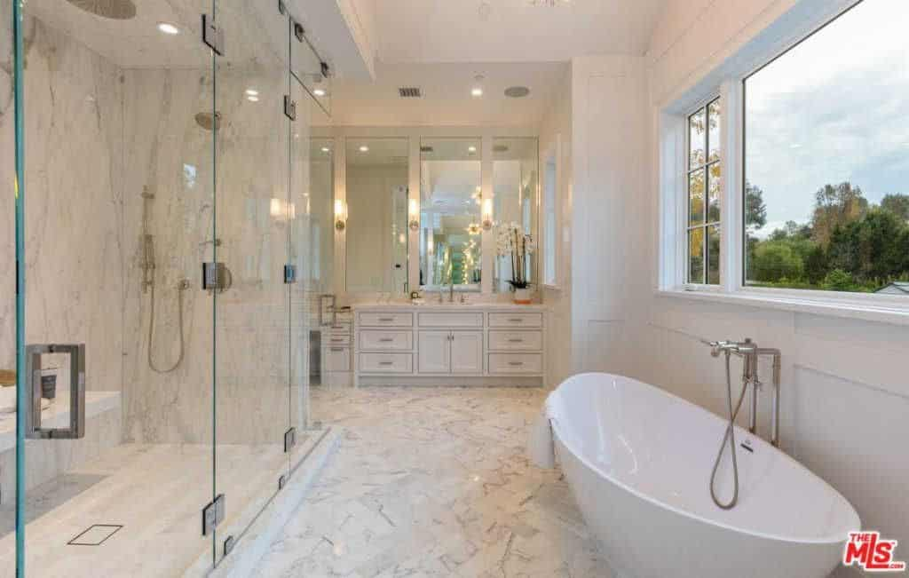 A pedestal tub is placed beneath the glazed windows in this master bathroom with a walk-in shower and white sink vanity paired with rectangular mirrors that are lighted by glass sconces.