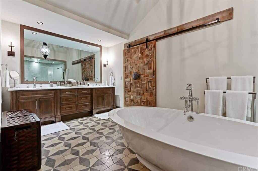 This master bathroom showcases wooden sink vanity and a freestanding tub fitted with chrome fixtures. It has vaulted ceiling and decorative tiled flooring topped by beige rugs.