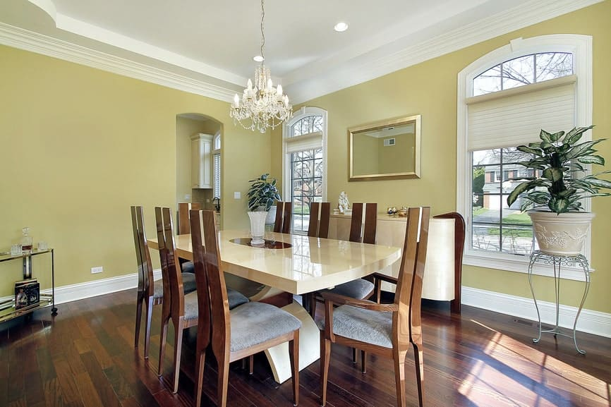 The modern dining table has a yellow creamy tone to it matches with the dining room cabinet that complements the yellow walls that stand out against the brilliant white ceiling that hangs a small crystal chandelier over over the hardwood flooring.