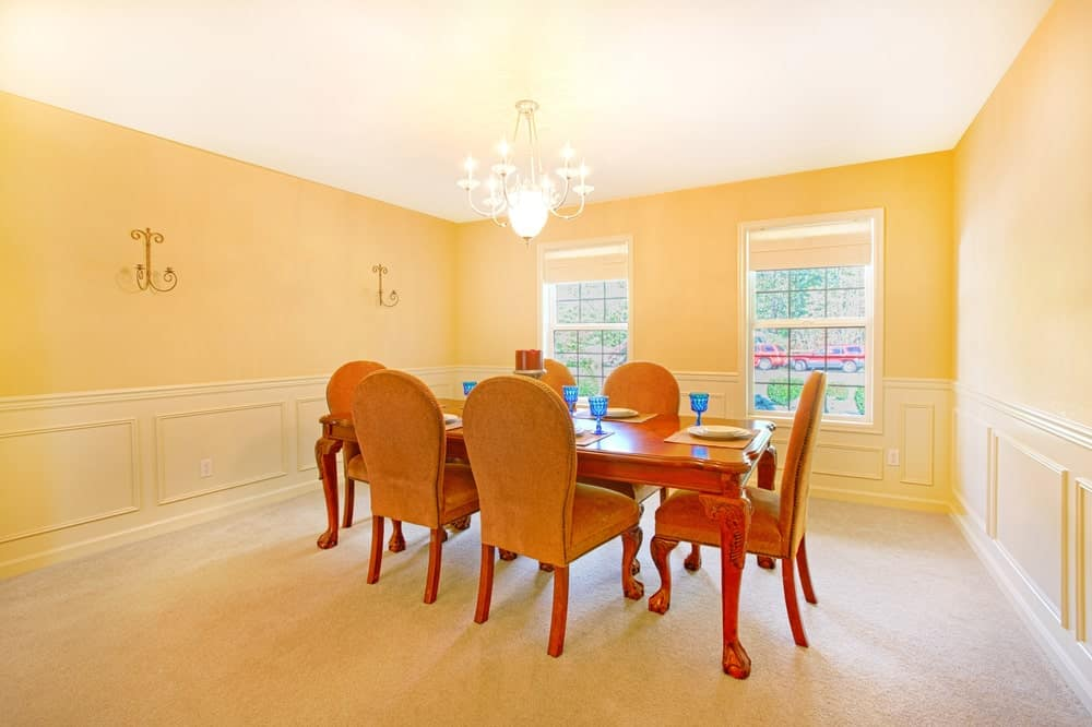 The walls of this simple dining room has a shiny and cheerful aura with its sunrise yellow walls and wainscoting in a slightly lighter shade of yellow for distinction. This matches with the beige carpeting that makes the wooden dining set stand out.