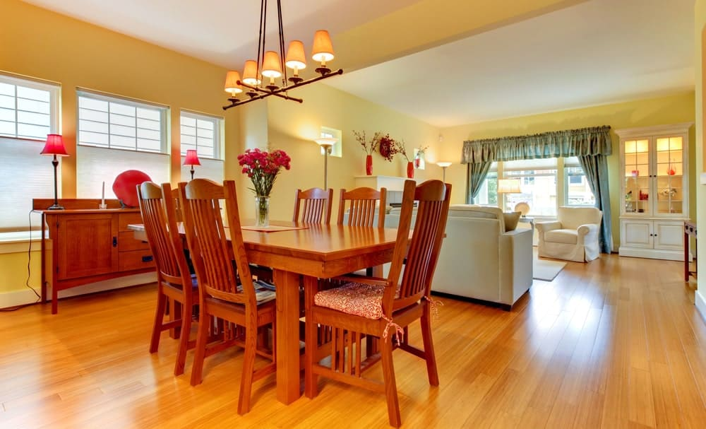 This dining area is part of a great room that also houses the living room within its yellow walls and hardwood flooring. This matches with the wooden dining set and the dining room cabinet by the windows bearing red decors and lamps.