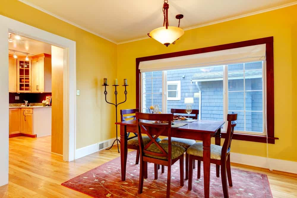 The hardwood flooring is covered with a charming area rug that has designs of flowers and vines in it. This matches with the redwood dining table and its cross back chairs as well as with the frame of the large window that stands out against the yellow walls.