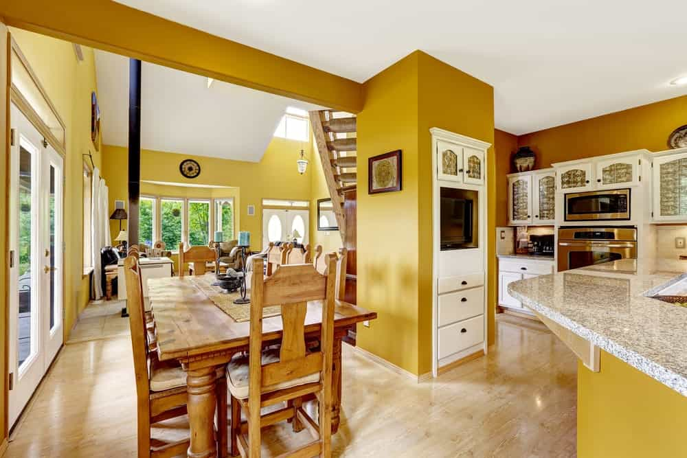 This informal dining room by the kitchen has mustard yellow walls that go great with the wooden rectangular dining table with elegant legs and its matching wooden chairs. These are brightened by glass doors and glass windows as well as a high white ceiling.