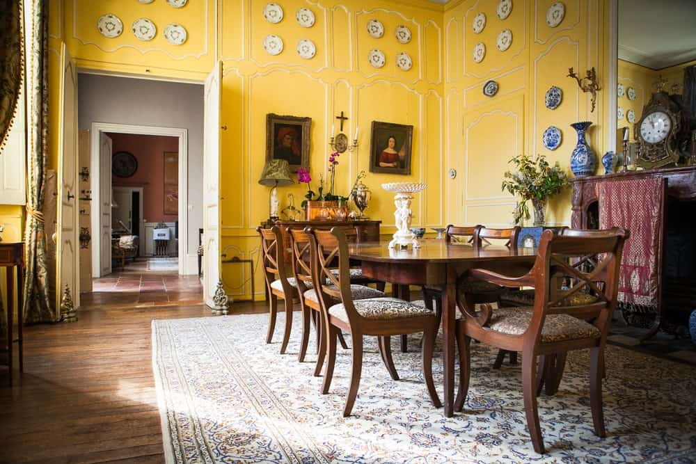 The elegant yellow wooden finish of the tall walls are accented with various classic paintings and decorative dishware. This sets the elegance level on high for the wooden dining table and its chairs over the large patterned area rug.