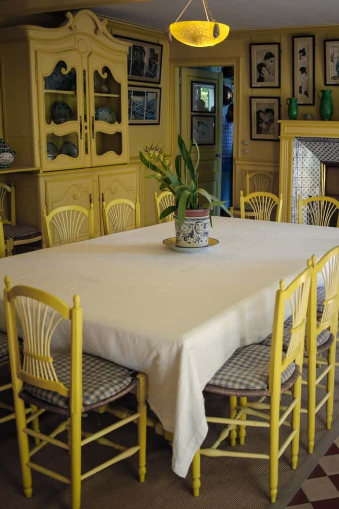 The yellow hues are the dominating force of this dining room with its yellow rustic chairs, yellow walls that blend with the yellow cabinets and yellow mantle for the fireplace by the head of the rectangular dining table with a tablecloth.