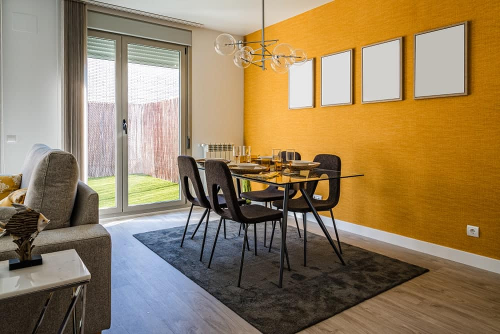 The yellow orange hue of the wallpaper is brightened by the natural lights coming in from the glass doors with a gray sliding curtain. The modern chandelier matches this as well as the glass-top dining table surrounded by modern dark chairs matching the area rug.