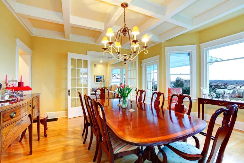 The white coffered ceiling supports an elegant chandelier that augments the yellow walls and warms up the wooden dining table that is surrounded with wooden chairs that have patterned colorful cushions.